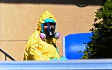 A member of the Hazmat crew carries a barrel down stairs from the apartment where Thomas Eric Duncan the Ebola patient was staying in Dallas, Texas on 3 October 2014. EPA/Larry Smith.
