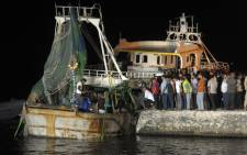 People gather on the quay as a wreck of a migrant boat raised by the Egyptian navy and maritime rescuers arrives in the Egyptian port city of Rosetta on 27 September 2016. Picture: AFP.
