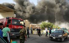 Members of the fire brigade and the Iraqi federal police stand outside the country's biggest ballot warehouse following a fire, in the capital Baghdad on 10 June, 2018. Picture: AFP