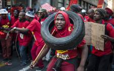 FILE: A striking worker wears a tyre around his neck as thousands of workers clad in red demonstrate on the first day of a nationwide strike called by Numsa to demand a pay raise and better working conditions. Picture:  AFP/MUJAHID SAFODIEN.