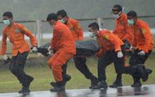 FILE:Members of an Indonesian search and rescue team transport the body of a victim from AirAsia flight QZ8501 recovered from the Java Sea in the rain at Pangkalan Bun in Central Kalimantan on 1 January, 2015. Picture: AFP.