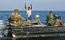 A fisherman raises his hands up to surrender as Uganda People's Defence Marine Force (UPDMF) stop him for fishing illegally, during a patrol on the lake Edward, on 13 August 2018, in Rwenshama, the Rukungiri District. Picture: AFP.