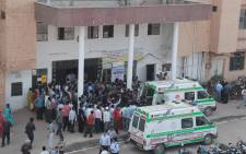 People watch as patients are shifted to ambulances outside the city hospital in Bilaspur, Chattisgarh, India, on 12 November 2014. Eleven women died and dozens took ill after doctors allegedly botched surgeries during a state-run sterilisation programme. Picture: EPA.