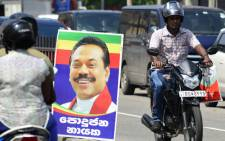 Sri Lankan motorcyclists ride past a poster of Mahinda Rajapakse's after he was sworn in as prime minister in Colombo on October 27, 2018. Sri Lanka President Maithripala Sirisena on October 27 suspended parliament, deepening political turmoil after he sacked the country's prime minister. Picture: AFP
