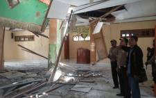 This handout from Indonesia's National Disaster Mitigation Agency (BNPB) taken on 27 February, 2018 shows local officials inspecting the damage to a mosque in Boven Digoel, Papua province, Indonesia, following a powerful earthquake in neighbouring Papua New Guinea. Picture: AFP