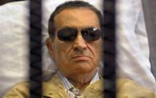Ousted Egyptian president Hosni Mubarak sits inside a cage in a courtroom during his verdict hearing in Cairo. Picture: AFP.