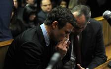 An emotional Oscar Pistorius is seen with his legal representative while appearing in the Pretoria Magistrate's Court on Monday, 19 August 2013 in connection with the murder of his girlfriend Reeva Steenkamp. Picture: Sapa.