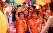 Visitors in traditional cheongsams take a selfie in a shop decorated for the Chinese Lunar New Year in Bangkok on 24 January 2020. Picture: AFP