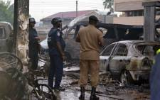 Policemen look at burnt vehicles at the scene where at least 90 people were killed in a petrol station fire in Ghana's capital, Accra, on 4 June, 2015. Picture: AFP.