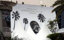 Workers install a giant banner at the Palais des Festivals et des Congres in Cannes, southeastern France, on 4 July 2021, two days before the start of the 74th Cannes Film Festival. Picture: Valery Hache/AFP