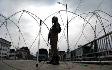 FILE: A security personnel stands guard on a street during a lockdown in Srinagar on 11 August 2019, after the Indian government stripped Jammu and Kashmir of its autonomy. Picture: AFP