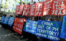 FILE: Filipino environmental activists display placards during a rally outside China's consular office in Manila on 11 May 2015, against China's reclamation and construction activities on islands and reefs in the Spratly Group of the South China Sea that are also claimed by the Philippines. Picture: AFP/Jay Directo.