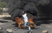 A protester throws rocks next to burning tyres during a demonstration on 6 July 2016, in Bulawayo Zimbabwe. Picture: AFP.