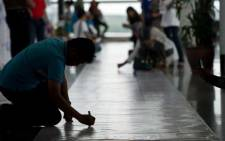 Visitors write on a banner carrying messages for the passengers of missing Malaysia Airlines flight MH370 at Kuala Lumpur International Airport on March 16, 2014. Picture: AFP.