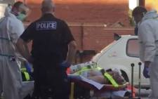 A still image taken from video footage recorded on 30 June 2018 and released to AFP on 5 July 2018 shows a man on a stretcher being put into an ambulance by medics and police outside a residential address in Amesbury, southern England, on 30 June 2018 where police reported a man and woman were found unconscious in circumstances that sparked a major incident after contact with what was later identified as the nerve agent Novichok. Picture: AFP.