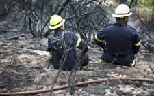 "Two firefighters ""take a load off"" after battling raging fires in Clovelly in the Cape. Picture: Thomas Holder/EWN"