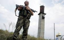 FILE: A Ukrainian soldier stands guard at a check-point near the eastern Ukrainian city of Donetsk on 11 August 2014. Picture: AFP.