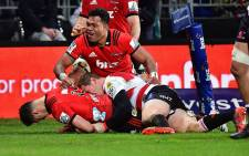 The Crusaders' David Havili (left) scores a try after being tackled by the Lions' Ruan Combrinck (centre right) as the Crusaders' Seta Tamanivalu (top) celebrates during the Super Rugby final at the AMI Stadium in Christchurch on 4 August, 2018. Picture: AFP