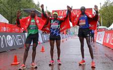 Third place, Ethiopia's Sisay Lemma (L), winner Ethiopia's Shura Kitata (C), and runner-up Kenya's Vincent Kipchumba (R) pose at the finish of the elite men's race of the 2020 London Marathon in central London on 4 October 2020. Picture: AFP.
