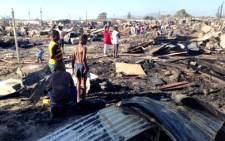 Children and their parents are seen walking around the burnt out remains of their Valhalla Park homes after a massive blaze. 23 December 2013. Picture: Rahima Essop/EWN.