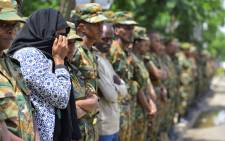 FILE: A woman mourns among soldiers standing guard ahead of the National funeral service, at the millennium hole in Addis Ababa, of Chief of Staff of the Ethiopian defence forces Seare Mekonnen and of Major-General Geza'e Abera, a retired former senior official in the Ethiopian army on 25 June 2019. Picture: AFP