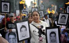 The parents of 43 missing students from Ayotzinapa teachers school hold their portraits and torches during a march 18 months after their disappearance in Mexico City on 26 April, 2016. Picture: AFP.