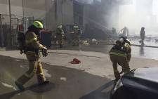 This handout photo released by the Metropolitan Fire Brigade (MFB) media shows firemen putting out a blaze from a light aircraft which exploded as it smashed into a shopping centre near Melbourne on 21 February 2017. Picture: AFP.