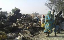 This handout image received courtesy of Doctors Without Border (MSF) on January 17, 2017, shows people standing next to destruction after an air force jet accidentally bombarded a camp for those displaced by Boko Haram Islamists, in Rann. Picture: AFP