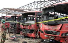 A soldier stands guard in front of burnt buses after an attack in Abuja, on 14 April, 2014. Picture: AFP.