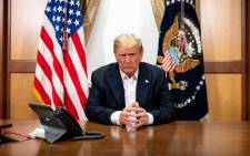 This handout photo released by the White House shows US President Donald Trump and his chief of staff (not pictured) participating in a phone call with the US vice president, secretary of state and chairman of the joint chiefs of staff on 4 October 2020, in his conference room at Walter Reed National Military Medical Center in Bethesda, Maryland. Picture: AFP.