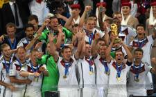 Germany's defender and captain Philipp Lahm (front 2R) holds up the World Cup trophy as he celebrates with his teammates after winning the 2014 Fifa World Cup final football match between Germany and Argentina 1-0. Picture: AFP