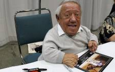 """This file photo taken on May 25, 2007 shows Star Wars actor Kenny Baker signs autographs during the opening day of """"Star Wars Celebration IV"""" in Los Angeles. Kenny Baker, the British actor who starred as plucky robot R2-D2 in the """"Star Wars"""" movies, died on August 13, 2016, his niece told local media. Picture: AFP."""
