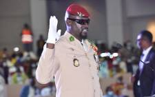 Guinea junta leader Colonel Mamady Doumbouya, raises his hand at his swearing-in ceremony as president of country transition on 1 October 2021 in Conakry. The head of the junta in Guinea, Colonel Mamady Doumbouya, was sworn in on Friday as president of this West African country for a period of transition of still unknown duration and content. Picture: Cellou Binani/AFP