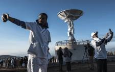People take selfie pictures in front of a satellite antenna during the ceremony for the launching of the Ethiopian Remote Sensing Satellite (ETRSS) in Entoto Observatory and Research Centre in Addis Ababa, on December 20, 2019. Picture: AFP.
