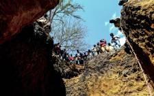 Illegal miners stand on top of a ditch where they search for rubies on 3 August 2018, in Nthoro village, on the outskirts of the mining town of Montepuez, Mozambique. Picture: AFP.