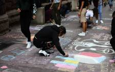High school students draw the Twin Towers and write messages on the sidewalk in front of their school on 11 September 2017 in New York, in observance of the 16th anniversary of the 11 September 2001 attacks. Picture: AFP