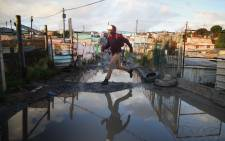 A Harare resident, jumps onto a piece of dry land as he makes his way home from work. Picture: Bertram Malgas