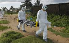 FILE: Liberian health workers in a burial squad carrying the body of an Ebola victim in Monrovia in September 2014. Picture: EPA