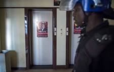 Police search the building for wanted MDC members. Picture: Thomas Holder/EWN.