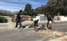 Sir Lowry's Pass Village residents removed rubble and torched debris from roads after a decision to abandon protest over houses in the area. Picture: Kevin Brandt/EWN