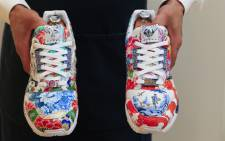 In this file photo an art handler from Sotheby's holds one-of-a-kind Sneakers by Adidas and Meisse named the ZX8000 Porcelain, during a preview at Sotheby's Auction House on December 4, 2020 in New York City. Picture: AFP.