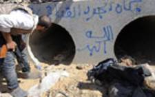 An NTC fighter looks through the concrete pipe where deposed Libyan leader Muammar Gaddafi was allegedly shot an captured during a gun battle on 20 October 2011 in Sirte. Picture: AFP