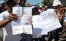 FILE: Lenasia residents show their council accounts, while demonstrating against houses built illegally in the area. Picture: EWN.