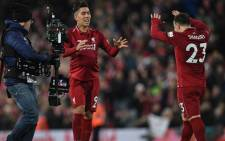 A television camera operator (L) films as Liverpool's Brazilian midfielder Roberto Firmino (C) celebrates with Liverpool's Swiss midfielder Xherdan Shaqiri following the English Premier League football match between Liverpool and Arsenal at Anfield in Liverpool, north west England on 29 December 2018. Liverpool won the match 5-1. Picture: AFP