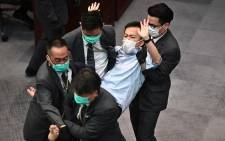 In this file photo taken on 8 May 2020, pro-democracy lawmaker Raymond Chan (C) is carried away by security following scuffles after pro-Beijing lawmaker Starry Lee (not seen) sat in the chairperson's seat before a key committee meeting at the Legislative Council in Hong Kong. Picture: AFP.