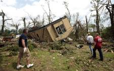 Volunteers help clean out Jean McAdams' mobile home after it was overturned by a tornado May 20, 2013 near Shawnee, Oklahoma. A series of tornados moved across central Oklahoma May 19, killing two people and injuring at least 21. Picture: AFP