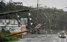 Cars drive past collapsed power lines, that partially block the road, as super typhoon Meranti skirts Pingtung county in southern Taiwan on 14 September 2016. Picture: AFP.