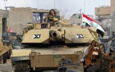 FILE: Iraqi counter-terrorism forces drive a tank past rubble south of the Anbar province's capital Ramadi on 24 December, 2015. Picture: AFP.