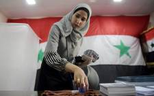 A Syrian woman casts her ballot at a polling station, decorated with huge national flags, in Aleppo on May 26, 2021 as voting began across Syria for an election guaranteed to return President Bashar al-Assad for a fourth term in office. Picture: AFP