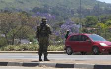 A soldier stands in the road in Manzini on 20 October 2021. At least 80 people were injured in Eswatini on 20 October 2021, a union leader said, as security forces cracked down on escalating pro-democracy protests in Africa's last absolute monarchy. Picture: AFP